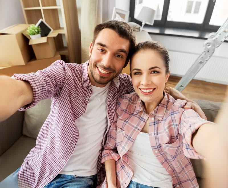 Szczęśliwa para bierze selfie przy nowym domem zdjęcie stock