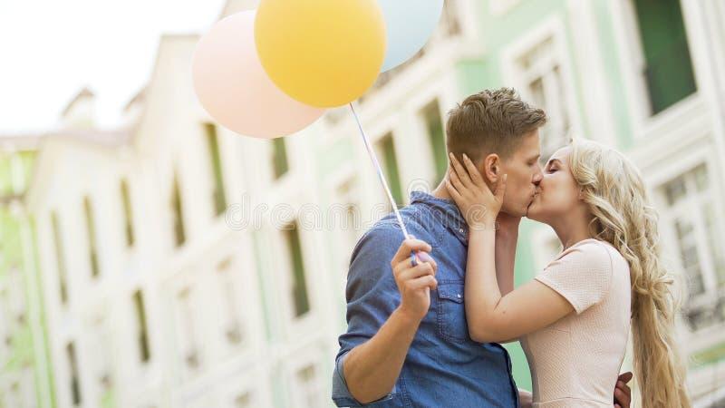 Szczęśliwa para całuje w ulicie z kolorowymi lotniczymi balonami, czuły związek obraz stock