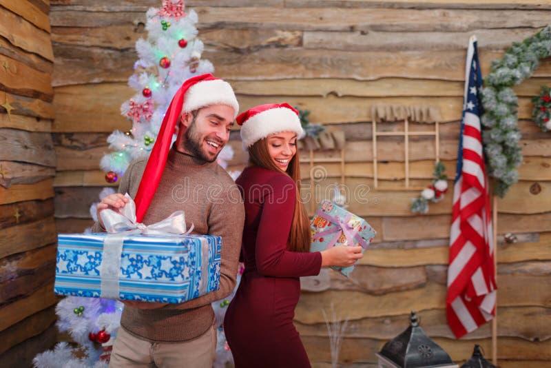 Szczęśliwa para dla nowego roku, stojak z prezentami each inny, z powrotem obraz stock
