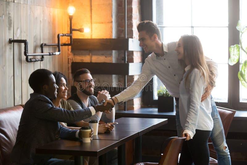Szczęśliwa para dostaje zaznajamiający z multiracial ludźmi przychodzi a zdjęcie royalty free