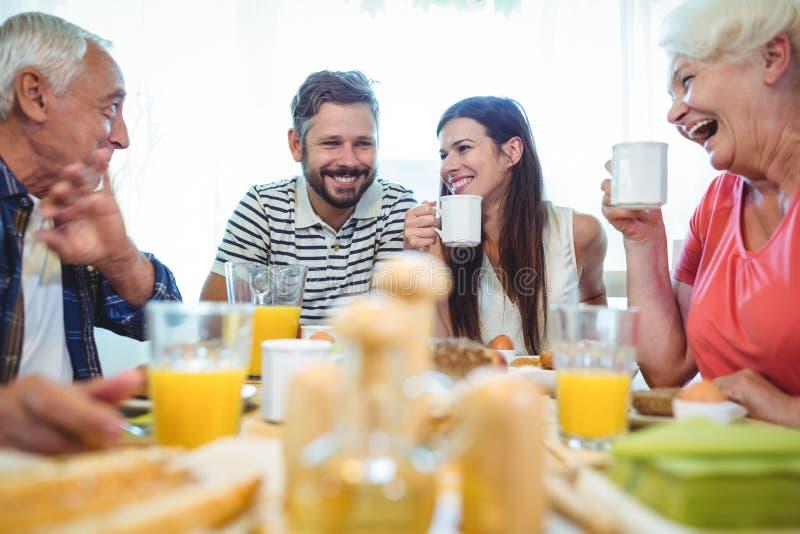 Szczęśliwa para i rodzice opowiada podczas gdy mieć śniadanie fotografia royalty free