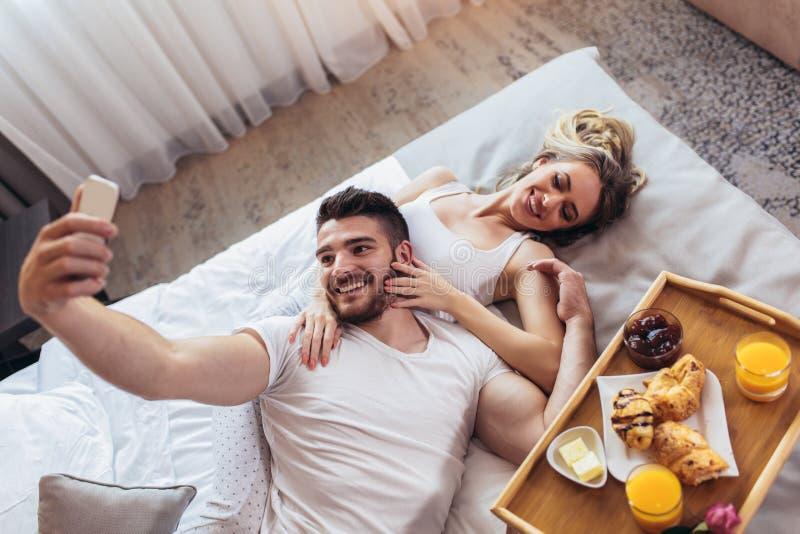 Szczęśliwa para ma śniadanie w luksusowego hotelu pokoju używać mądrze telefon brać selfie fotografię obrazy stock