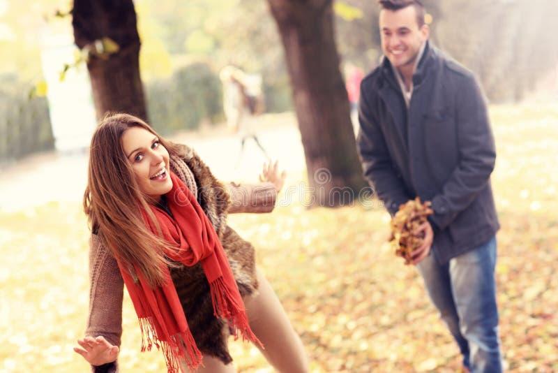 Szczęśliwa para ma zabawę w parku w jesieni obraz royalty free