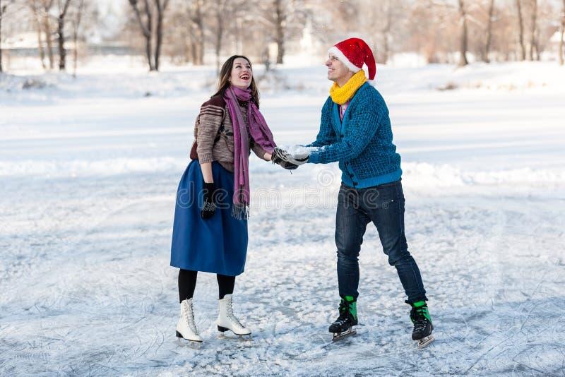 Szczęśliwa para ma zabawy jazda na łyżwach na lodowisku outdoors obrazy royalty free
