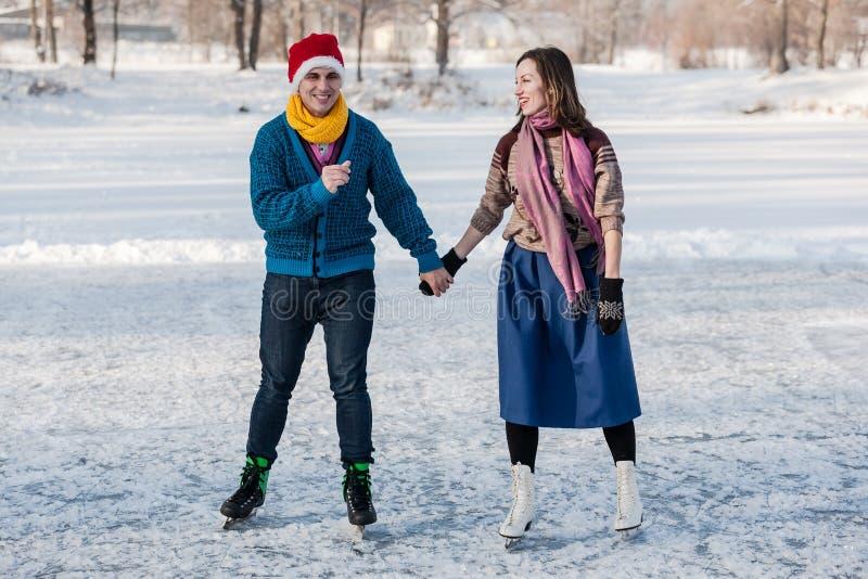 Szczęśliwa para ma zabawy jazda na łyżwach na lodowisku outdoors obraz stock