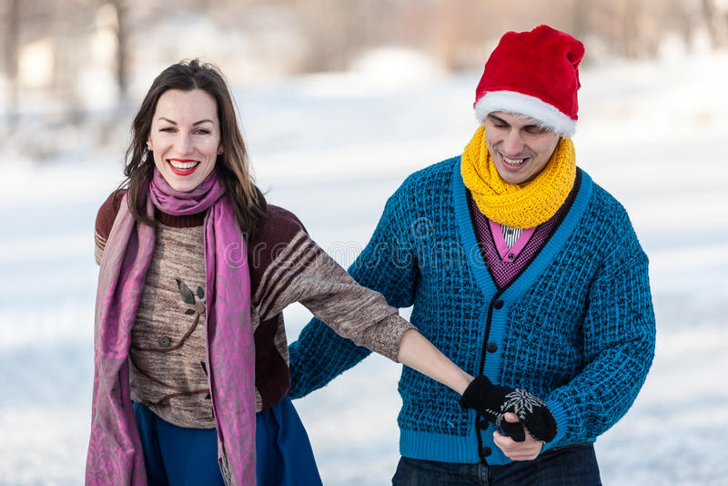 Szczęśliwa para ma zabawy jazda na łyżwach na lodowisku outdoors zdjęcie stock