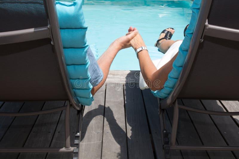 Szczęśliwa para na basenów bocznych krzesłach ma zabawę fotografia royalty free