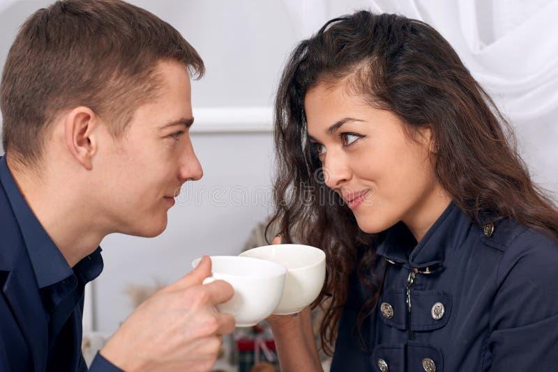 Szczęśliwa para opowiada herbaty w pokoju i pije obraz stock