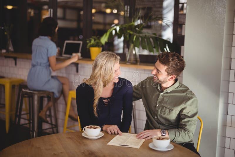 Szczęśliwa para opowiada podczas gdy siedzący z filiżankami i menu przy stołem obraz stock