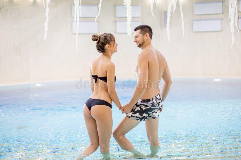 Szczęśliwa para opowiada w basenie obraz stock