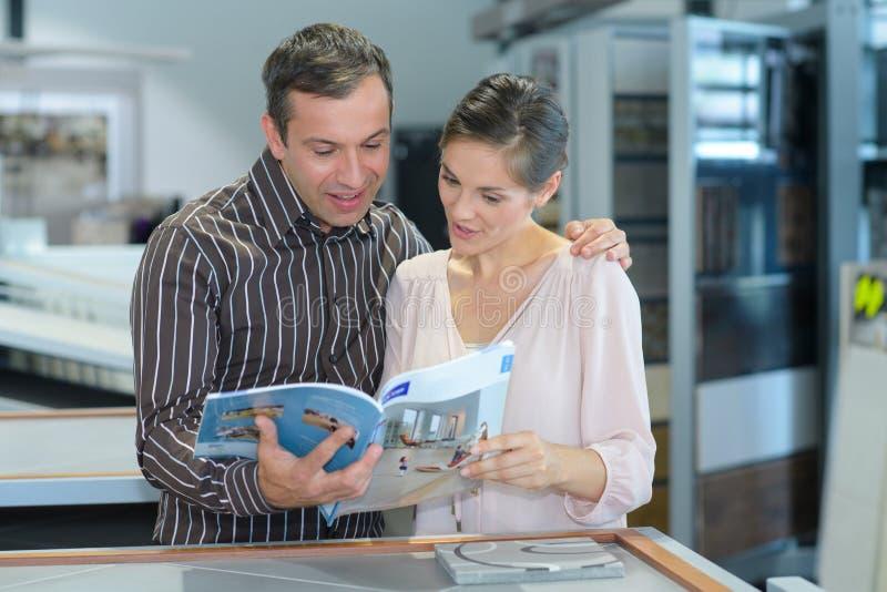 Szczęśliwa para patrzeje katalog w meblarskim sklepie fotografia royalty free