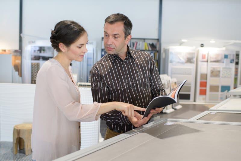 Szczęśliwa para patrzeje katalog w sklepie obraz stock