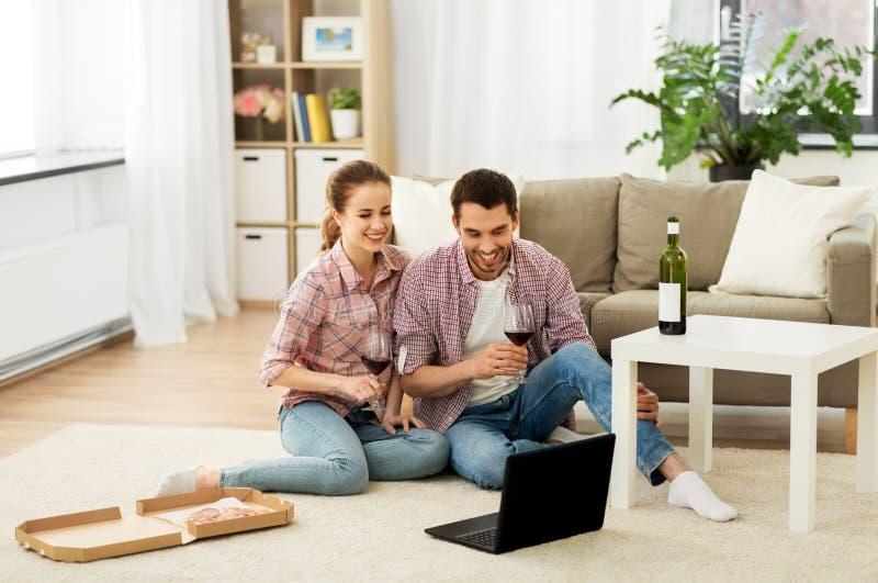 Szczęśliwa para pije czerwone wino w domu z laptopem zdjęcie royalty free