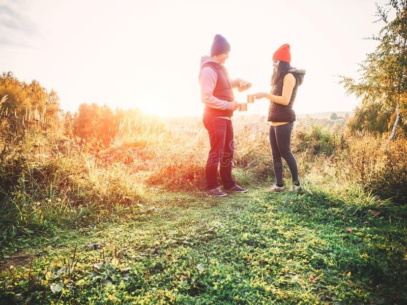 Szczęśliwa para pije herbaty outdoors uśmiecha się śmiać się w przypadkowych ubraniach na naturze, mieć pinkin w sezonie jesienny obraz stock