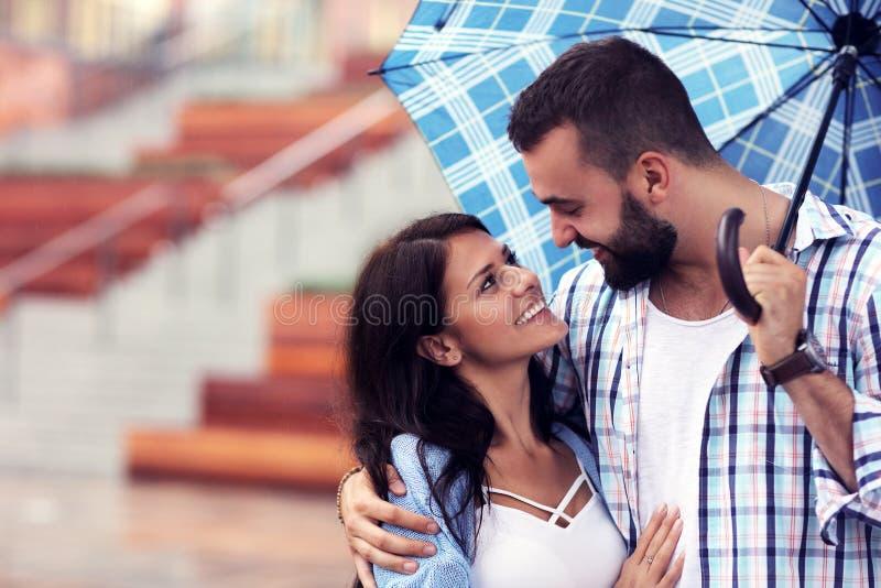 Szczęśliwa para pod parasolem w mieście zdjęcie royalty free