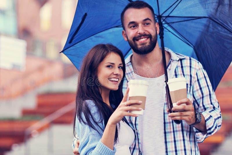 Szczęśliwa para pod parasolem w mieście obrazy royalty free