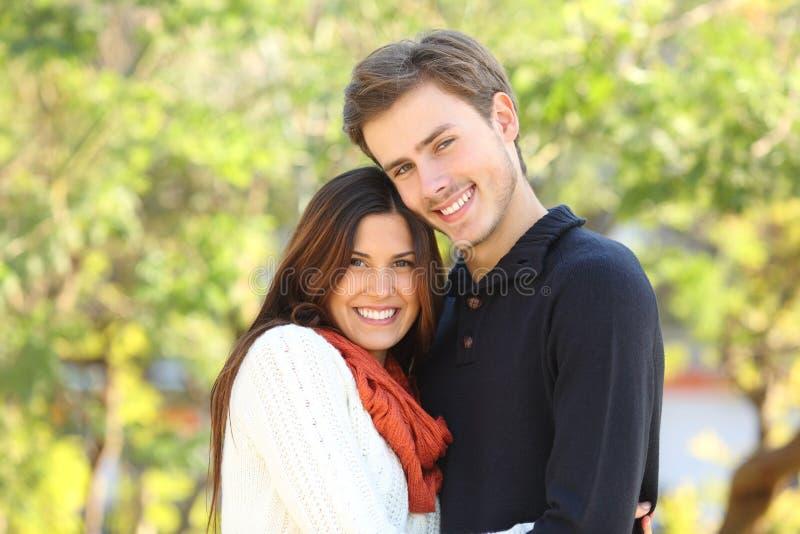 Szczęśliwa para pozuje patrzejący ciebie w parku obrazy stock