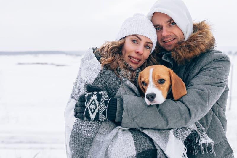 Szczęśliwa para przy zima krajobrazu Szczęśliwą rodziną z beagle psem godziny krajobrazu sezonu zimę zdjęcie royalty free