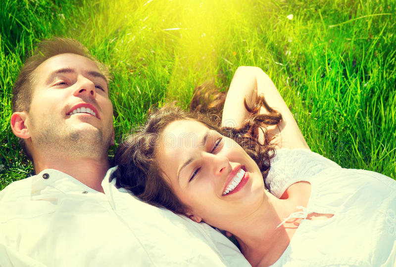Szczęśliwa para relaksuje na zielonej trawie zdjęcia royalty free