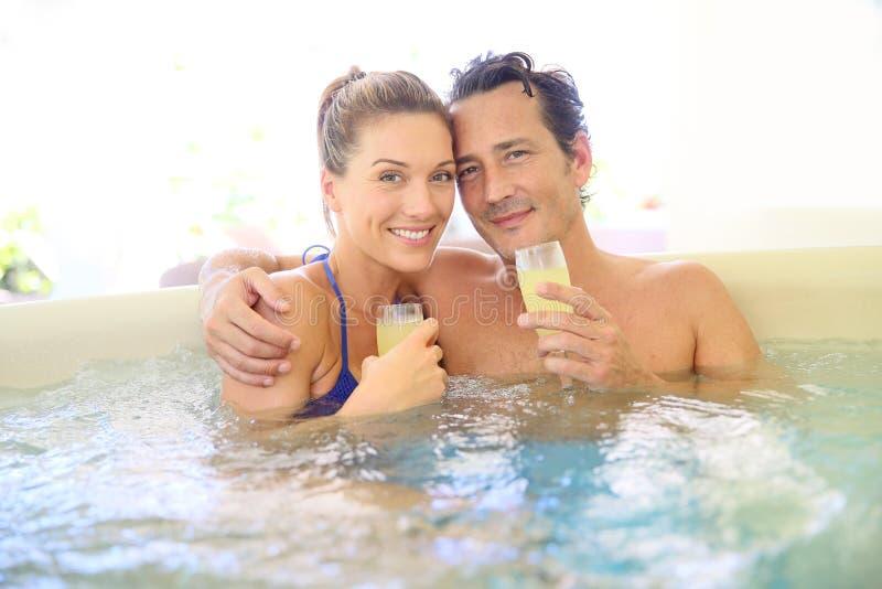 Szczęśliwa para robi grzance z szampanem w jacuzzi fotografia stock