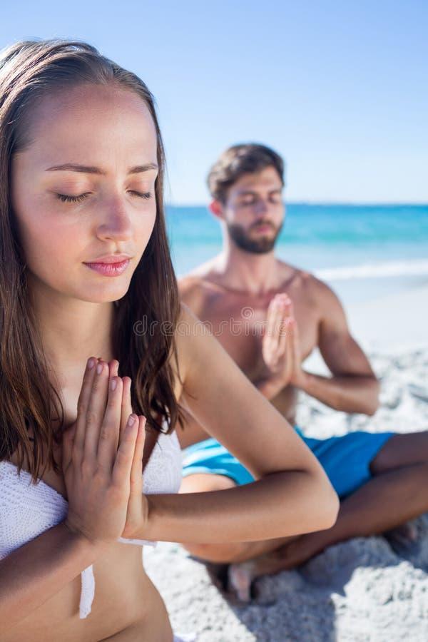 Szczęśliwa para robi joga obok wody zdjęcie royalty free