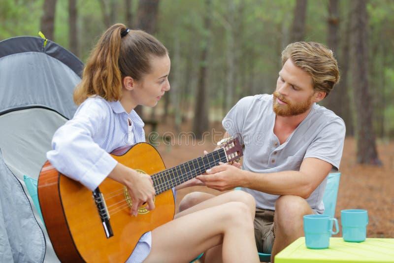 Szczęśliwa para siedzi blisko namiotu z gitarą obraz stock