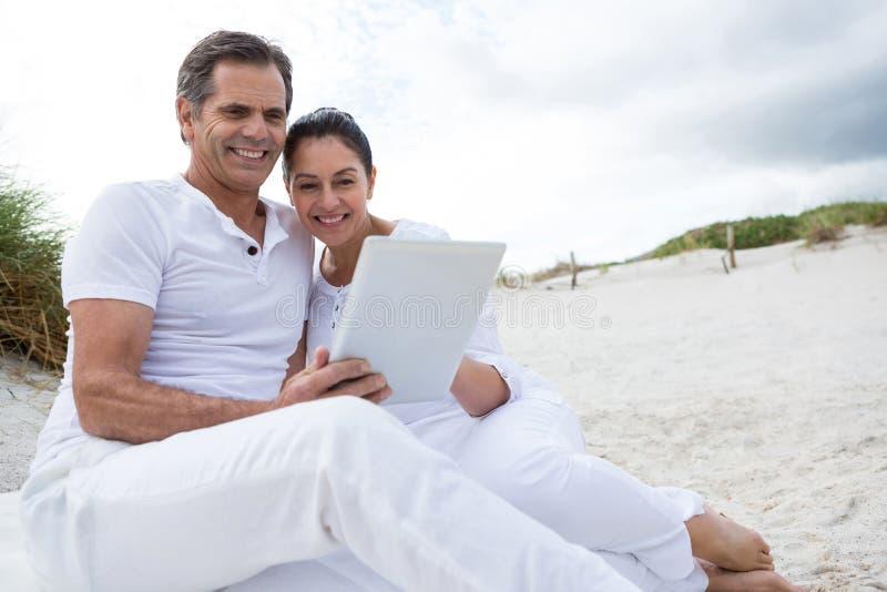 Szczęśliwa para używa cyfrową pastylkę na plaży fotografia stock