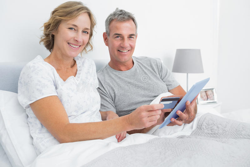 Szczęśliwa para używa ich pastylka komputer osobistego kupować online fotografia royalty free