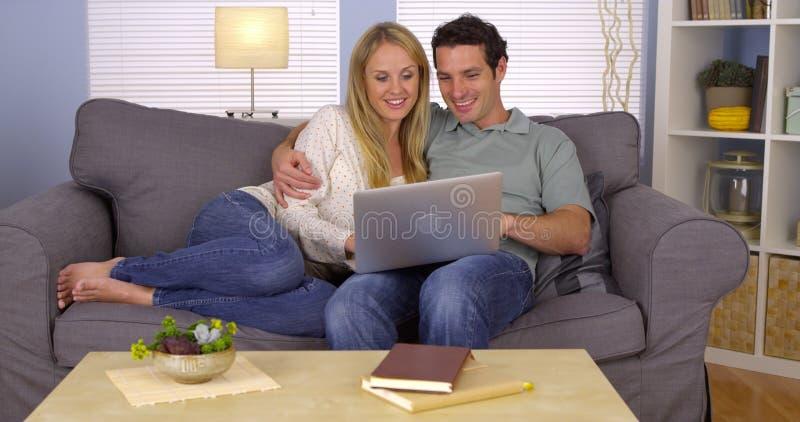 Szczęśliwa para używa laptop na leżance obraz stock