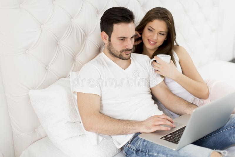 Szczęśliwa para używa laptopu lying on the beach na ich łóżku w domu zdjęcie royalty free