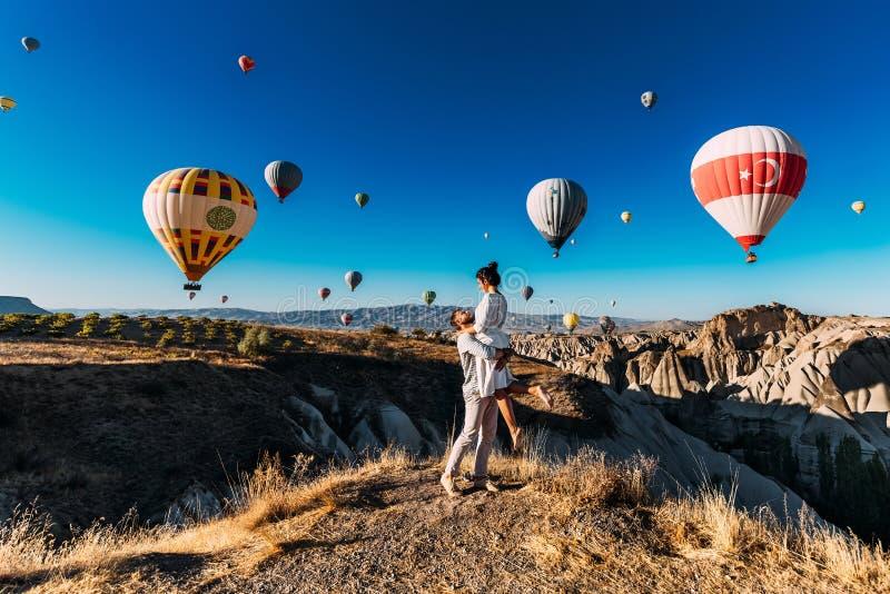 Szczęśliwa para w Cappadocia Mężczyzna proponujący dziewczyna Miesiąc miodowy w Cappadocia Para przy balonowym festiwalem Par pod obrazy stock