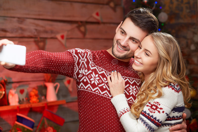 Szczęśliwa para w ciepłych pulowerach bierze selfie obrazek w bożych narodzeniach zdjęcia stock