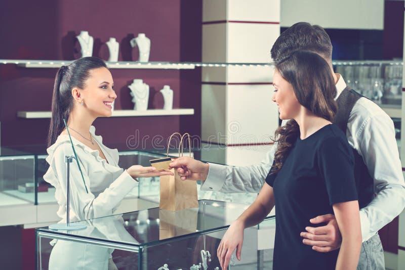 Szczęśliwa para w miłości płaci z kredytową kartą przy biżuterii stora zdjęcie stock