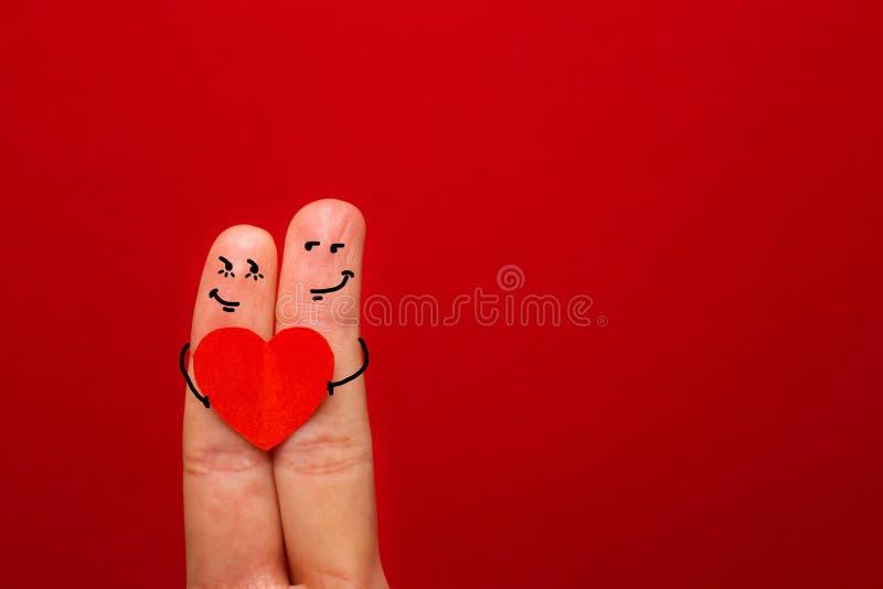 Szczęśliwa para w miłości z malującym smiley mienia czerwonym sercem - wizerunek zdjęcia royalty free