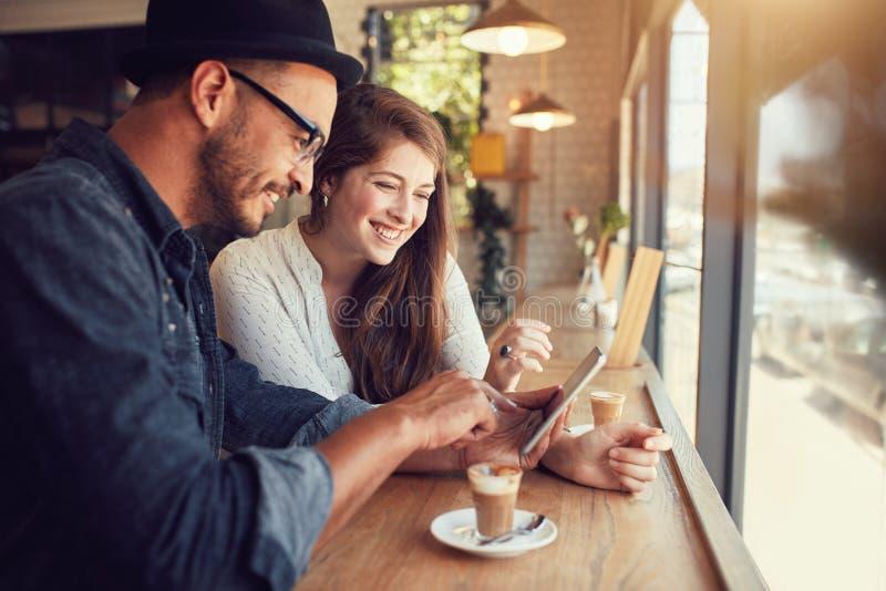 Szczęśliwa para w sklep z kawą używać cyfrową pastylkę zdjęcia stock