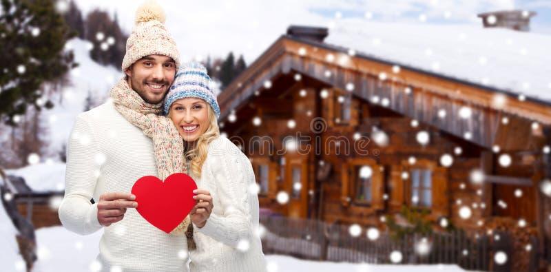Szczęśliwa para w zimie odziewa z sercem outdoors zdjęcie royalty free