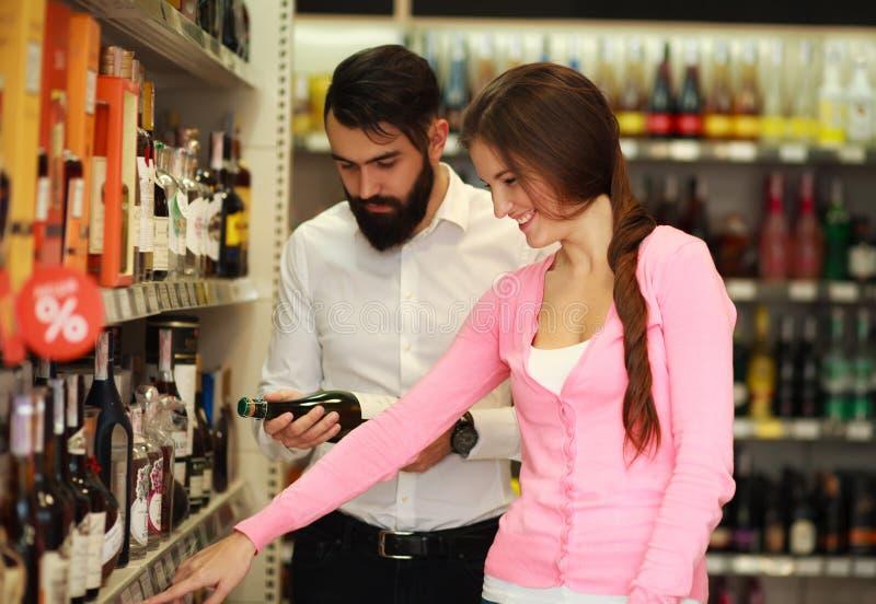 Szczęśliwa para wybiera alkohol od gablota wystawowa sklepu obrazy stock