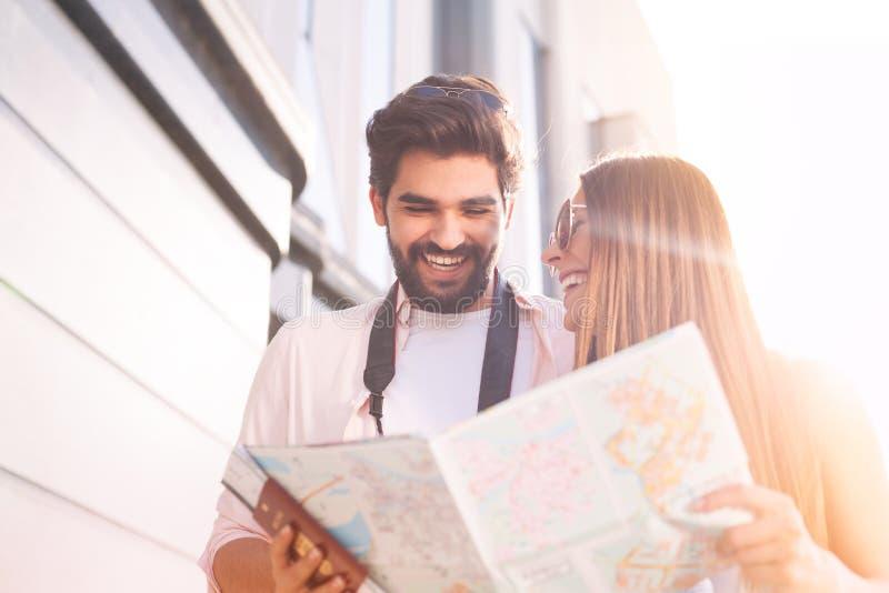 Szczęśliwa para wybiera pierwszy miejsce przeznaczenia z mapą zdjęcie stock