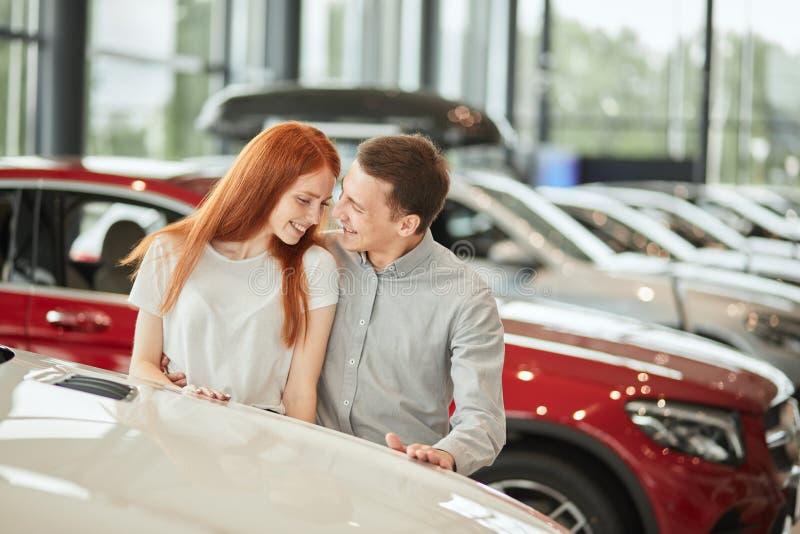 Szczęśliwa para wybiera pierwszy rodzinnego samochód kupować w sala wystawowej fotografia royalty free