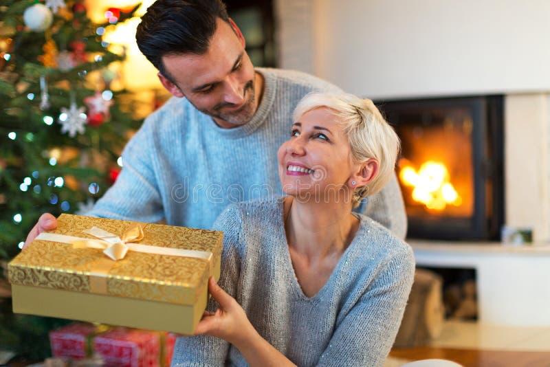 Szczęśliwa para z Bożenarodzeniowym prezentem w domu fotografia royalty free