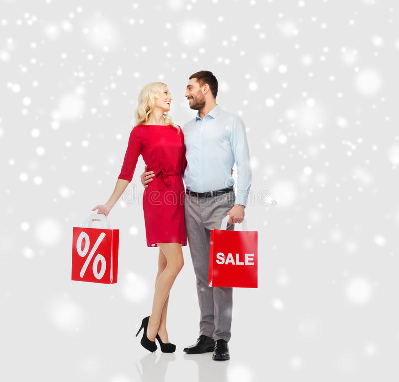 Szczęśliwa para z czerwonymi torba na zakupy nad śniegiem zdjęcie stock