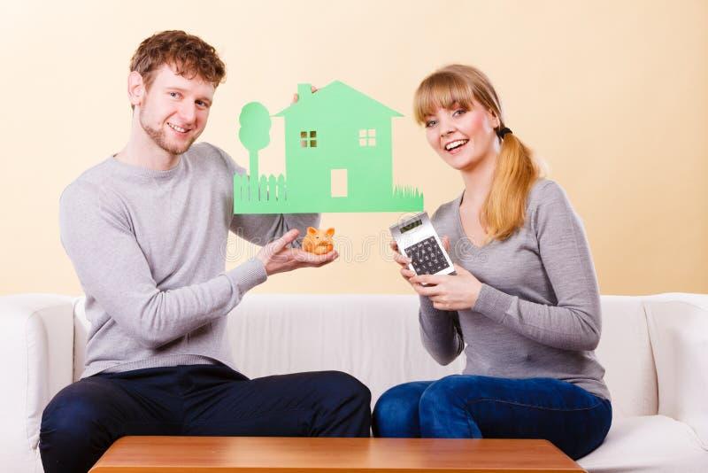 Szczęśliwa para z domem i kalkulator zdjęcia stock