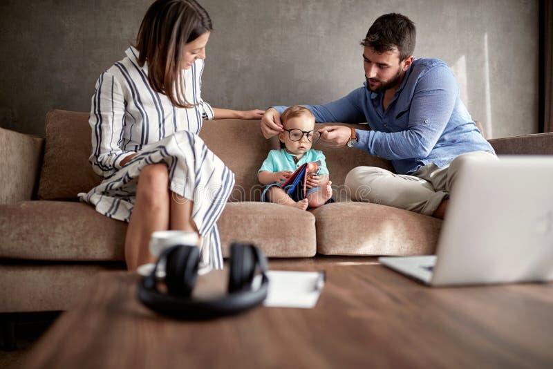 Szczęśliwa para z ich chłopiec bawić się i czytelnicza książka przy hom zdjęcia royalty free