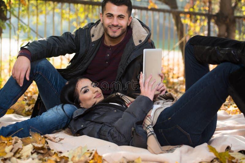 Szczęśliwa para Z pastylka komputerem W parku obrazy stock