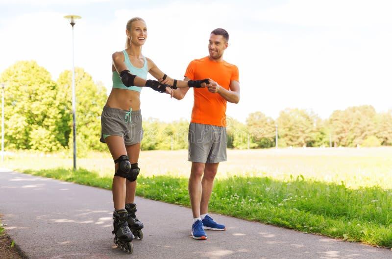 Szczęśliwa para z rolkowymi łyżwami jedzie outdoors obraz royalty free