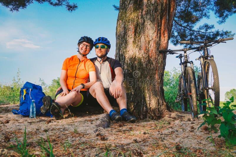 Szczęśliwa para z rowerem górskim siedzi obejmowanie czasu wolnego naturę outdoors szczęśliwa para, prowadzi aktywnego styl życia zdjęcia royalty free