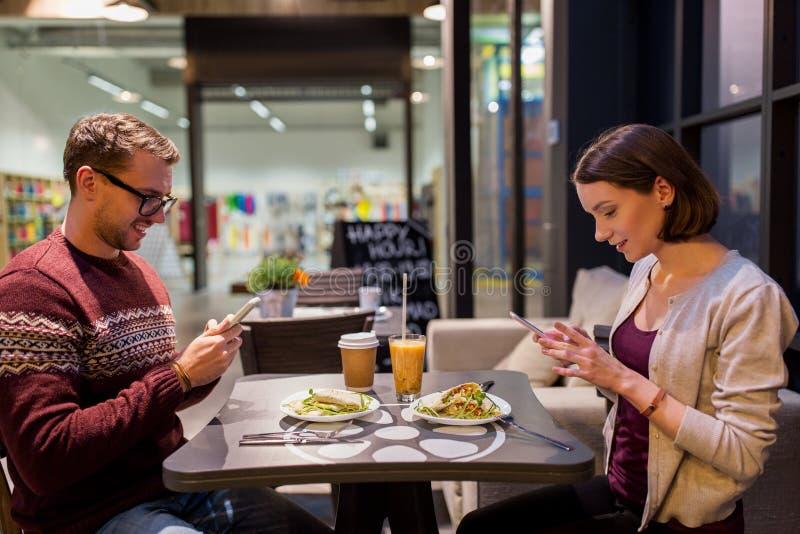 Szczęśliwa para z smartphones przy weganin restauracją obraz stock