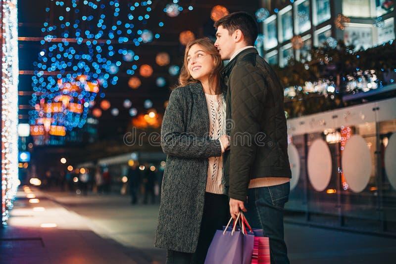 Szczęśliwa para z torba na zakupy cieszy się noc przy miasta tłem fotografia stock