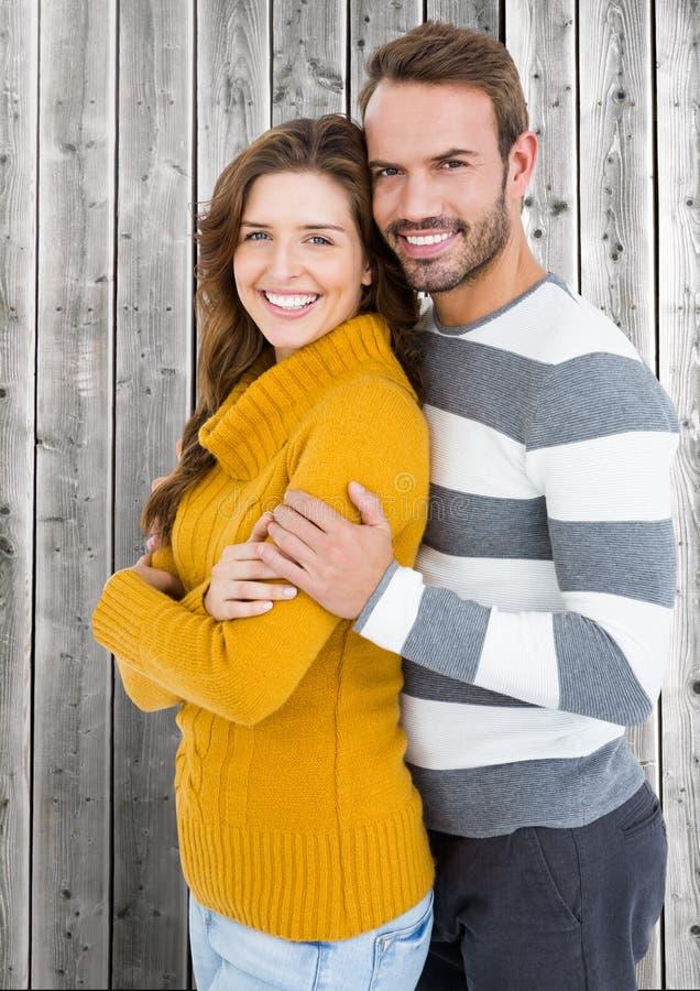 Szczęśliwa pary pozycja przed drewnianym tłem obrazy royalty free