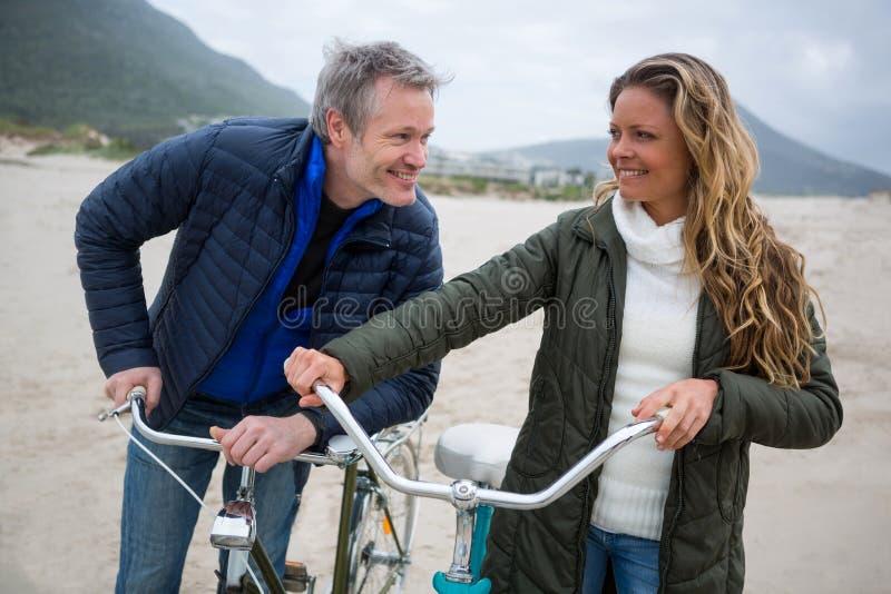 Szczęśliwa pary pozycja z bicyklem na plaży obraz royalty free